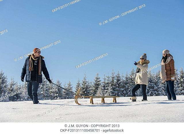 Young man pulling snow sledge winter countryside female girlfriends
