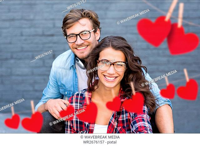 Composite image of red hanging heart and couple embracing each other