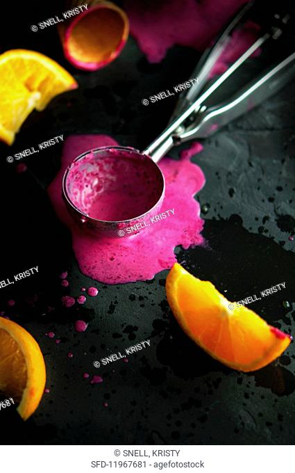 An ice cream scoop with melted berry sorbet and oranges