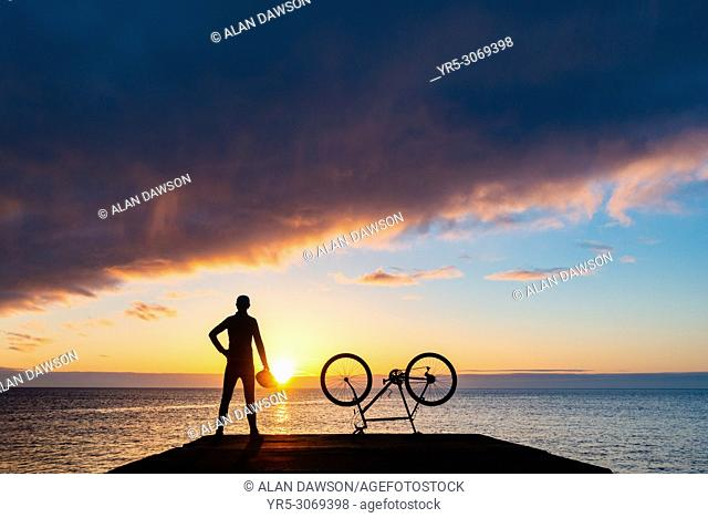 Seaton Carew, County Durham, north east England. United Kingdom. A mountain biker looks out over the North sea at sunrise