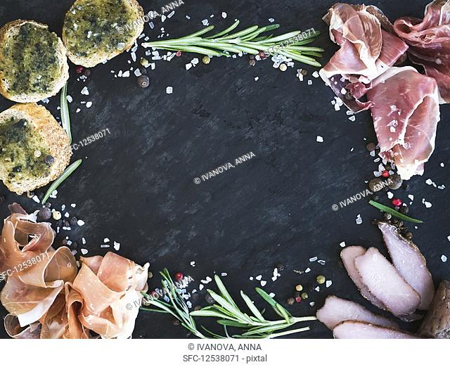 A still life of appetisers with crostini, prosciutto, rosemary and spices