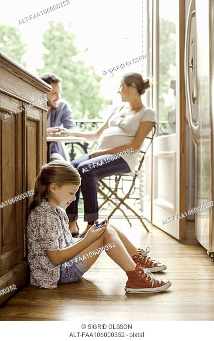Girl engrossed in video game while parents chat in background