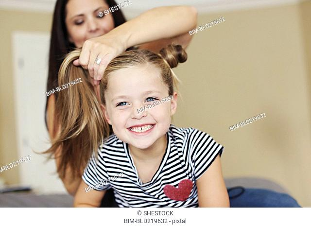 Mother styling hair of daughter on bed