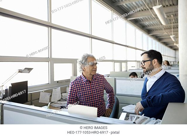 Businessmen discussing in office cubicle