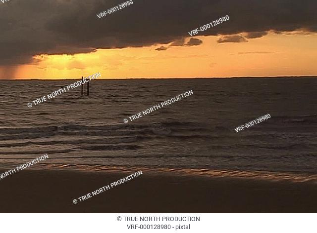 GV, MS, sea lapping shore, calm, dusk, cloudy, red sky, tranquil. Spurn Point, UK