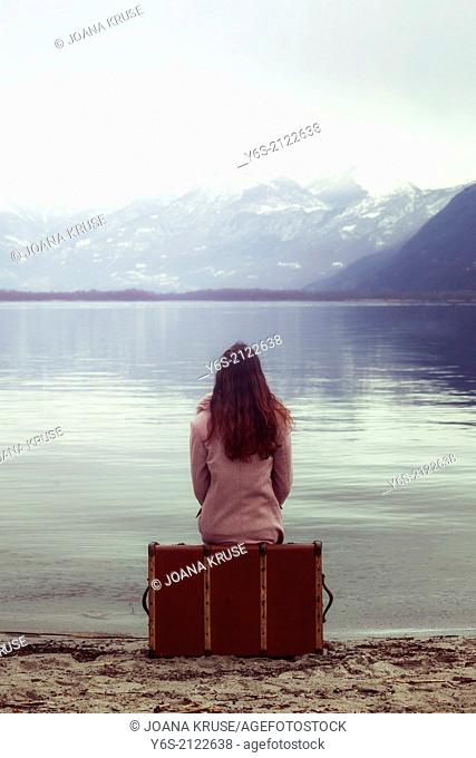 a woman in a pink dress sitting on a suitcase at a lake