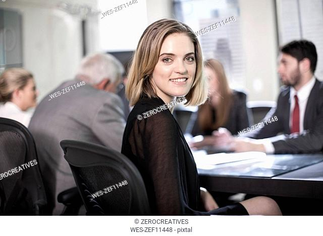 Successful businesswoman sitting in conference, looking at camera