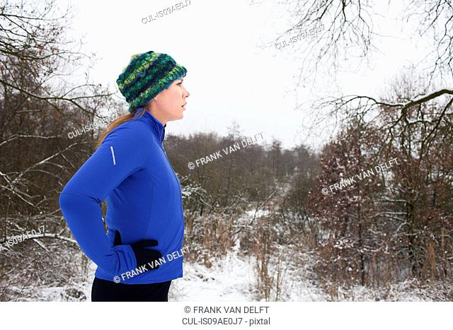 Female runner taking a break in winter scene