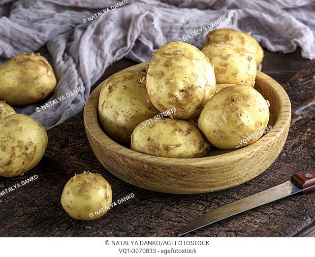 young potatoes in the peel lay in a wooden bowl on a brown table, close up