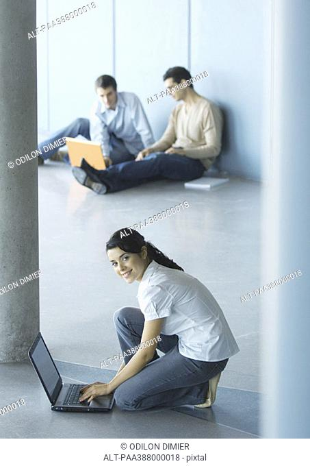 Young woman crouching sitting on floor, using laptop, men sitting in background