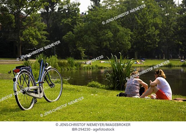 Two women sitting in a park, Vondelpark, Amsterdam, Netherlands