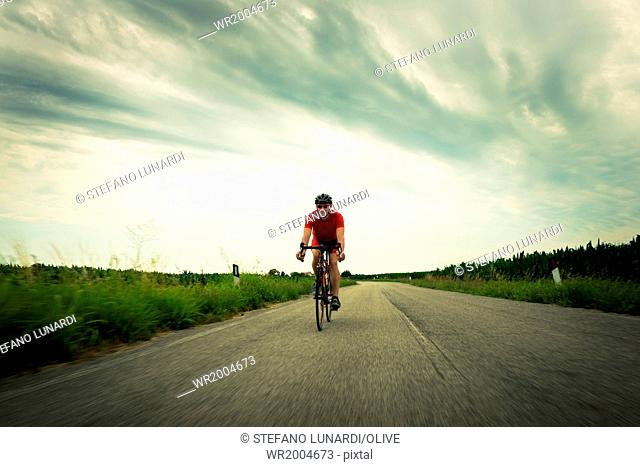 Cyclist riding on country road