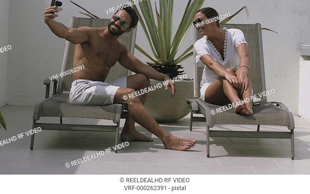 Man sitting on sun lounger and taking photograph of woman using digital camera