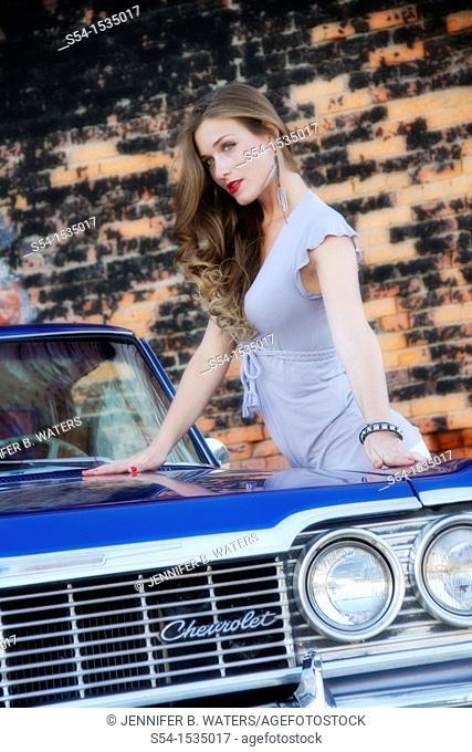 A young woman with a 1964 Chevrolet Impala in Spokane, Washington, USA