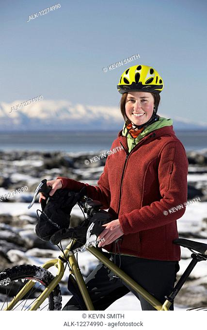 Young woman with her bicycle standing on frozen ice chunks along the Tony Knowles Coastal Trail, Anchorage, Southcentral Alaska