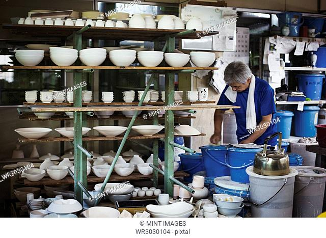 Man standing in a Japanese porcelain workshop with shelves of various porcelain bowls