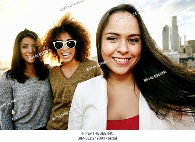 Portrait of smiling women on urban rooftop at sunset