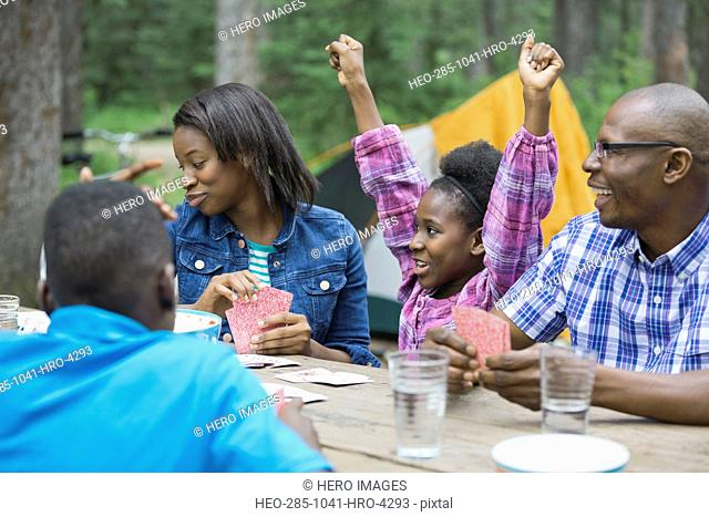 Girl winning card game while playing with family while camping