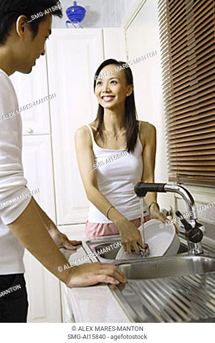 Couple in kitchen, man washing dishes, smiling at woman