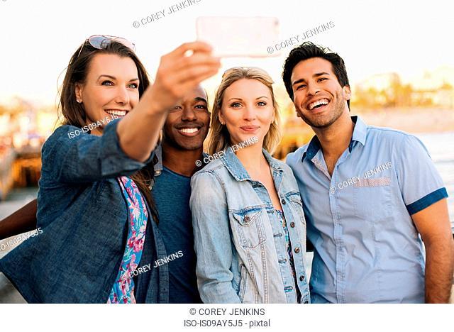 Adult friends taking smartphone selfie on pier, Santa Monica, California, USA