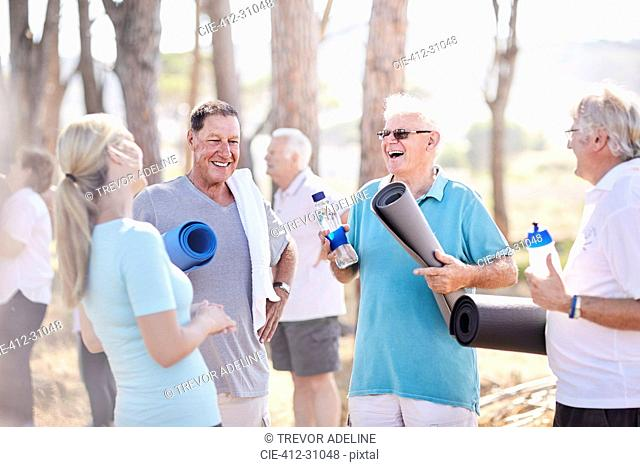 Yoga instructor talking to senior men after class in park