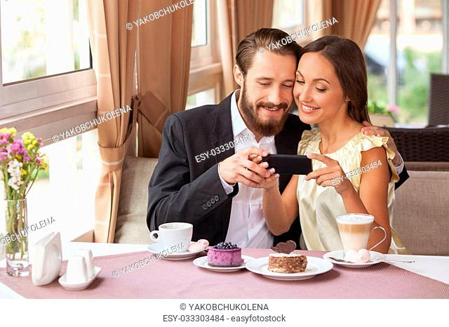 Cheerful young loving couple is making selfie in restaurant. They are sitting and looking at the mobile phone happily. The man and woman are embracing and...