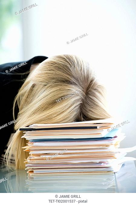 Businesswoman sleeping on stack of files