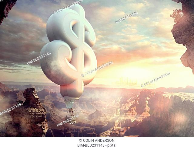 Mixed Race man floating in dollar sign hot air balloon at sunset