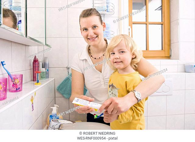 Mother helping daughter for brushing teeth, smiling, portrait