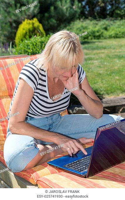 Blonde middle aged woman is sitting on the lounger outdoors and looking to the open notebook