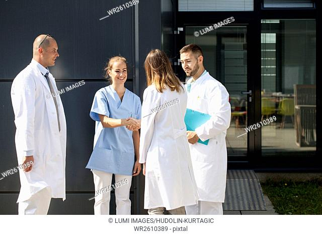 Female Doctor shaking hands with nurse outdoors