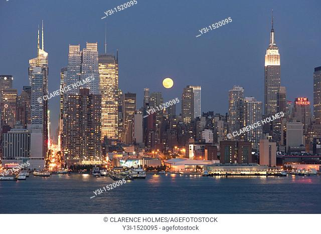 The full moon rises over the Manhattan skyline at twilight as viewed over the Hudson River from New Jersey
