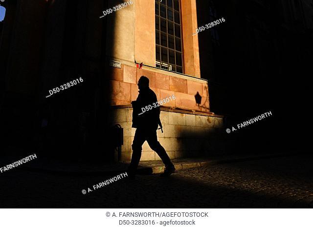 Stockholm, Sweden People walking in deep sunset shadows near Storkyrkan on Gamla Stan or Old Town