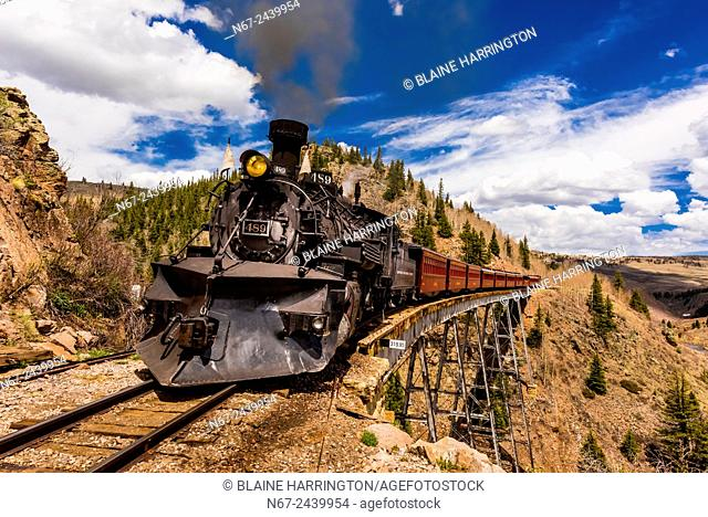 The Cumbres & Toltec Scenic Railroad train pulled by a steam locomotive crosses the Cascade Trestle (over Cascade Creek) on the 64 mile run between Antonito