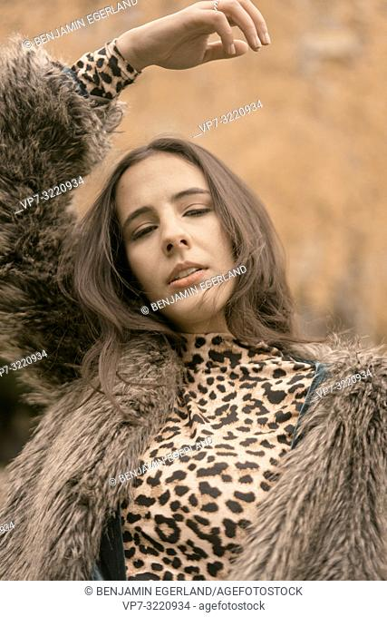 portrait of playful woman with fashionable clothes, expressing desire and sensual emotions, autumn season, dreamer, day dreaming, in Munich, Germany