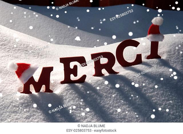 Red Letters With Santa Hat On White Snow With Snowflakes As Christmas Card. French Text Or Word Merci Mean Thank You. Snowy Scenery And Atmosphere