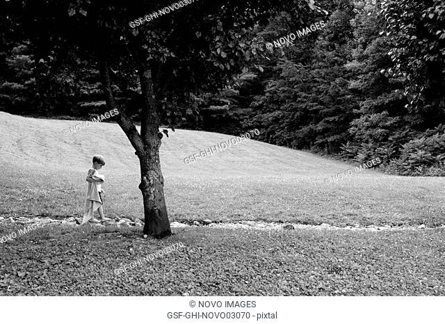 Boy with Blanket Walking Along Rocky Path
