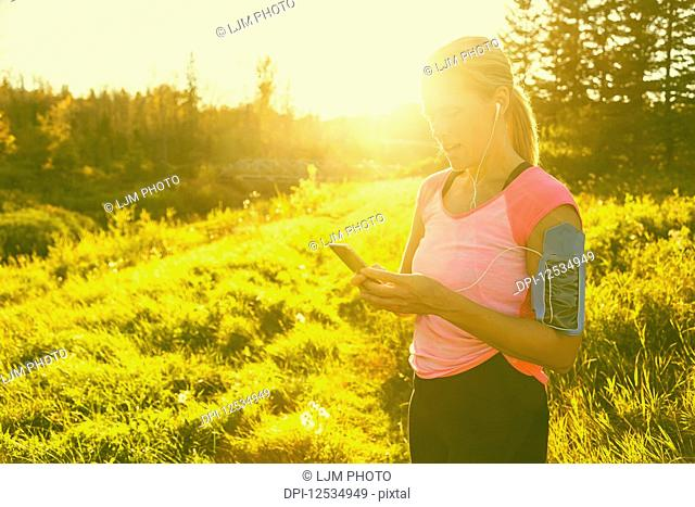 An attractive middle-aged woman wearing active wear pauses to text message while out running beside a creek in a city park on a warm fall evening and listening...