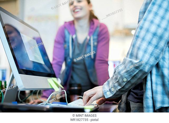 Two people at a computer repair shop, one typing and checking a monitor display