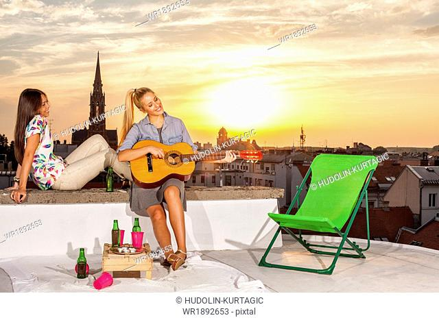 Young woman with girlfriend at rooftop party playing guitar