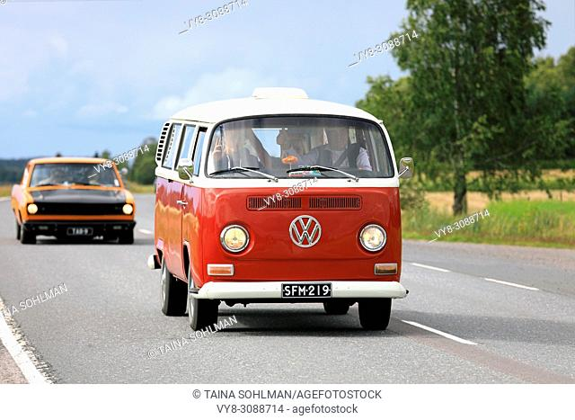 Classic Volkswagen red and white Type 2 camper van moves along highway on Maisemaruise 2017 car cruise summer event in Tawastia Proper, Finland
