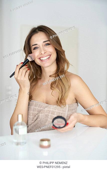 Portrait of smiling young woman applying make-up
