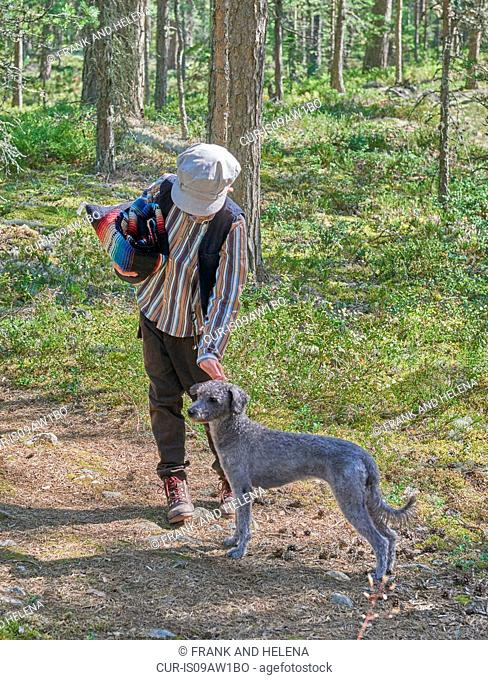 Boy wearing retro clothes with dog in forest