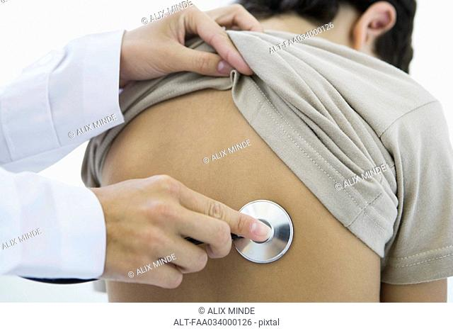 Doctor holding stethoscope against boy's back, cropped view