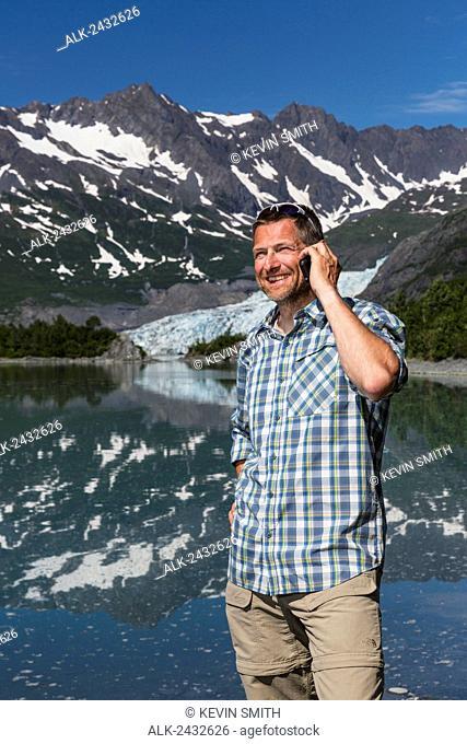 Man talking on a smartphone in front of Shoup Bay, Shoup Bay State Marine Park, Prince William Sound, Valdez, Southcentral Alaska