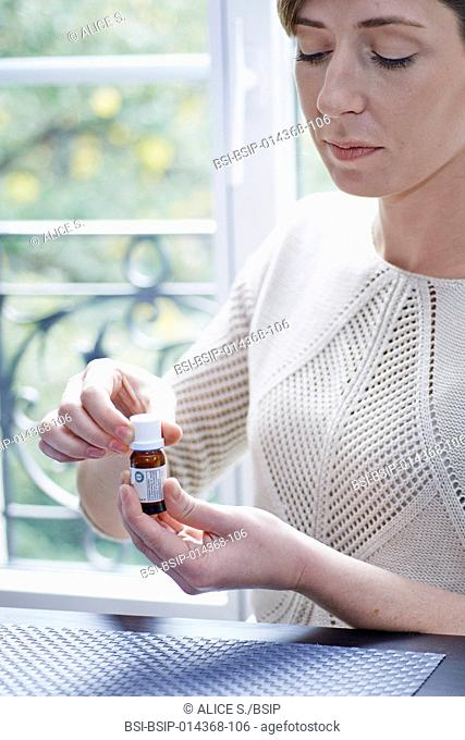 woman holding a bottle of essential oil