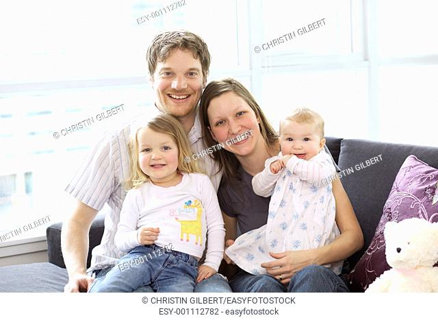 Portrait of happy family relaxing in the living room at home