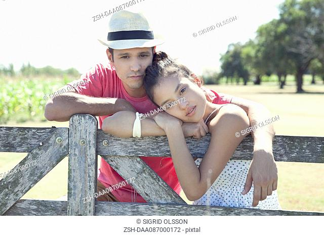 Young couple learning against wooden fence, portrait