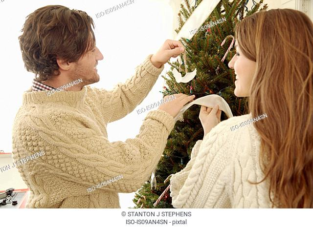 Young couple putting decorations on christmas tree