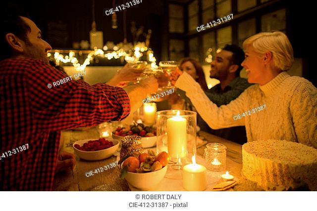 Friends toasting champagne glasses at candlelight Christmas dinner party
